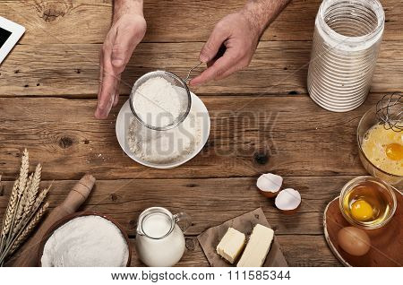 Male Baker Sifts The Flour On A Wooden Table