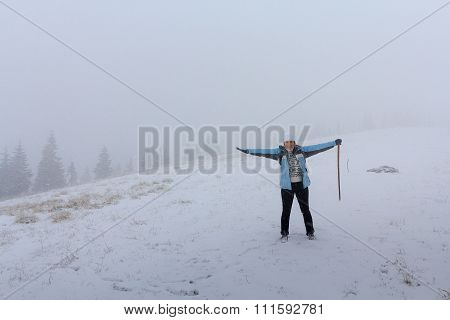 Girl In A Jacket On A Hillside In A Strong Snowstorm. Winter