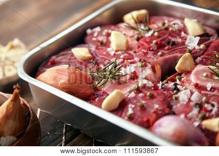 Closeup Meat In Steel Pan With Spices Ready To Cook On Table