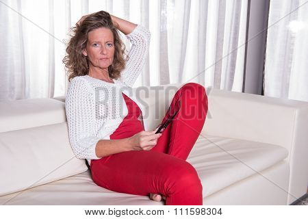 Attractive Woman Sitting On Couch And Thinking