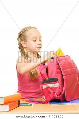 Schoolgirl is packing her rucksack