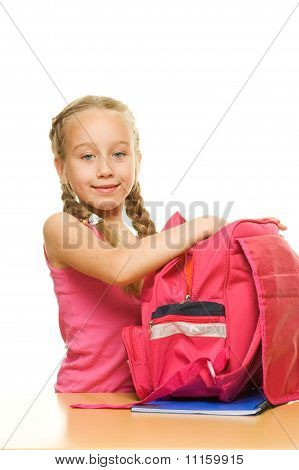 Little beautiful schoolgirl is packing her rucksack