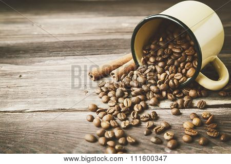 Coffee Beans Spilled Out Of The Old Cup. Vintage Style Photo.