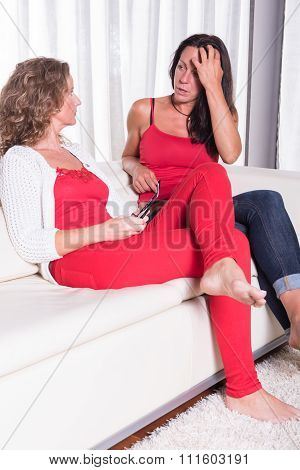 Two Attractive Women Sitiing On The Couch And Talking