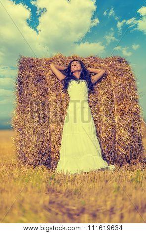 Brunette Woman Near Hay Bale