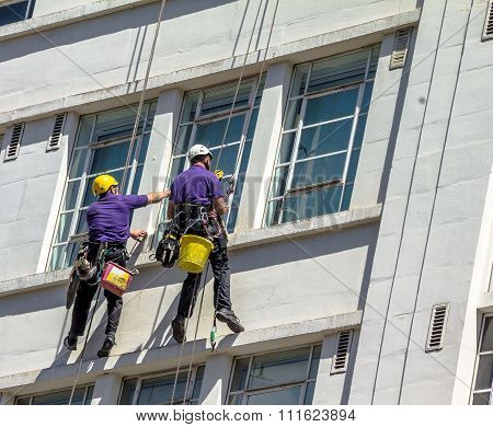 Unidentified Washers Wash The Windows Of Old Building In Central London. Uk