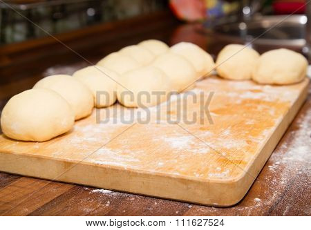The Cut Dough For Pies Against A Kitchen Table-top