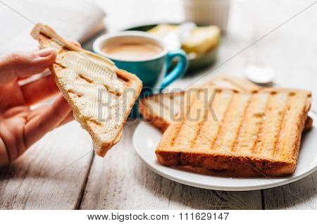 Woman Hand Eating Toast For Breakfast