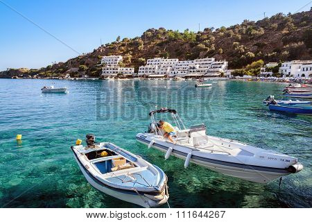 Man makes a repair of motorboat in bay of Loutro town