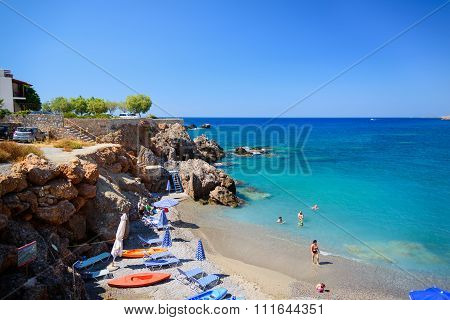 ourists sunbathing and swimming in blue lagoon of Chora Sfakion town at Crete island