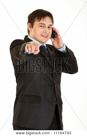 Smiling young businessman talking on mobile phone and pointing finger at you isolated on white