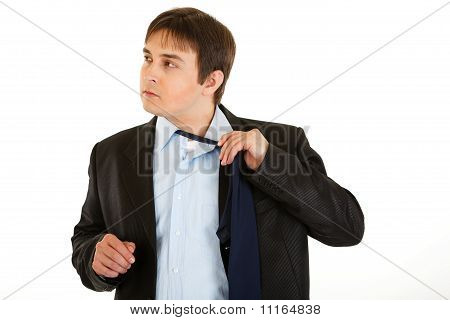 Tired young businessman untying his tie isolated on white