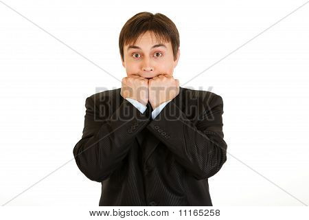 Scared young businessman holding hands near mouth isolated on white