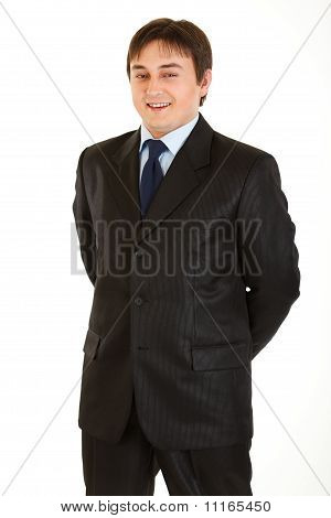 Smiling young businessman with hands behind his back isolated on white