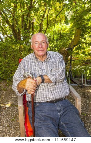 Happy Laughing Senior Sitting In His Chair In The Garden