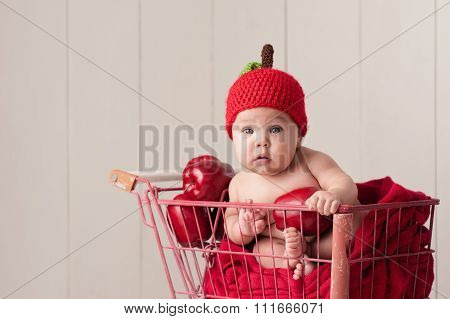 Baby Sitting In A Shopping Cart Wearing An Apple Hat