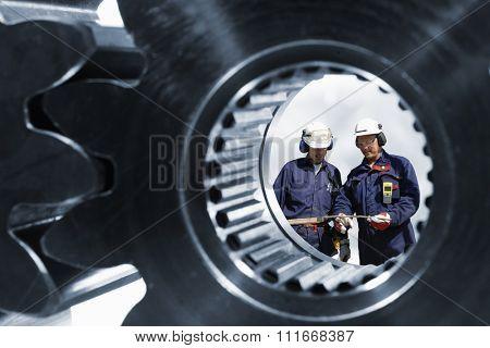 engineers, workers seen through a large cogwheels axle