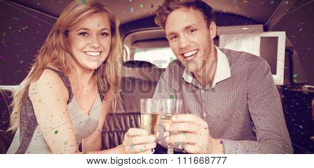 Flying colours against happy couple drinking champagne in limousine