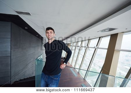 portrait of young successful startup business man in penthouse,  modern bright duplex office apartment interior  with staircase and big windows