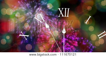 Clock counting down to midnight against colourful fireworks exploding on black background