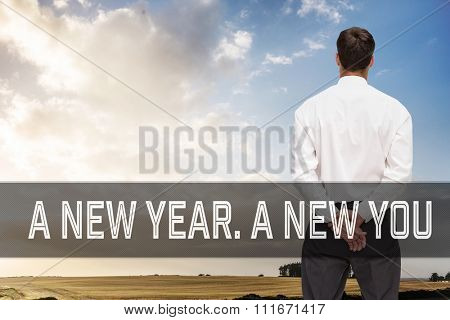 Motivational new years message against composite image of businessman turning his back to camera