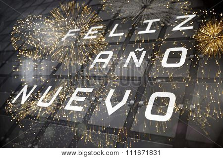 Colourful fireworks exploding on black background against new year message on black roller board in spanish