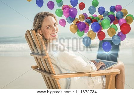 Gorgeous blonde sitting on deck chair using laptop on beach against colourful balloons