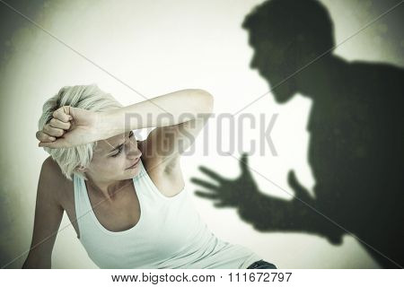 Depressed woman on the floor against silhouette of shouting man