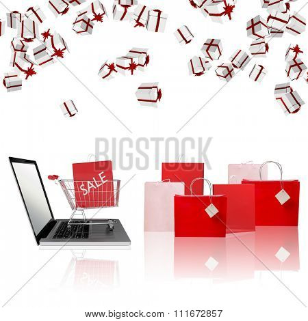 Trolley on laptop with sale bag against gift bag