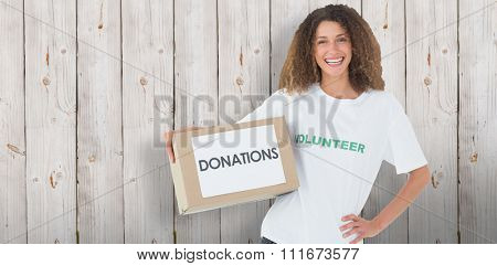 Smiling volunteer holding a box of donations with hand on hip against wooden background