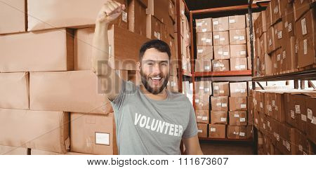 Portrait of cheerful volunteer against shelves with boxes in warehouse
