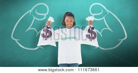 Smiling volunteer woman holding money bags against green chalkboard