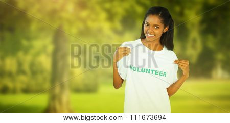 Young woman wearing volunteer tshirt and pointing to it against trees and meadow