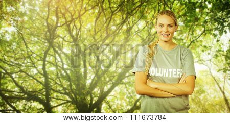 Portrait of beautiful smiling woman with arms crossed against green leaves