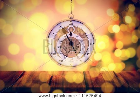 Hanging pocketwatch against desk with christmas tree in background