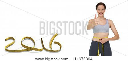 Fit woman measuring waist while gesturing thumbs up against white background with vignette