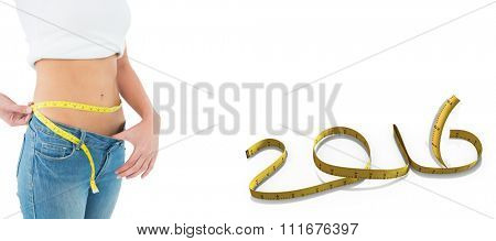 Mid section of a woman measuring waist in a big sized jeans against white background with vignette