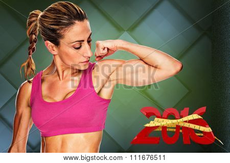 Female bodybuilder flexing bicep in pink sports bra against dark grey room