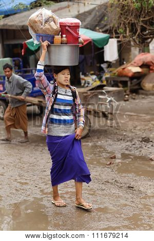 AMARAPURA, MYANMAR, JANUARY 17, 2015 : A woman is carrying a large metallic container on her head, walking in the dirty street of the Zegyo market, in Mandalay, Myanmar (Burma).