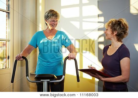 Trainer With Eldery Woman On Treadmill