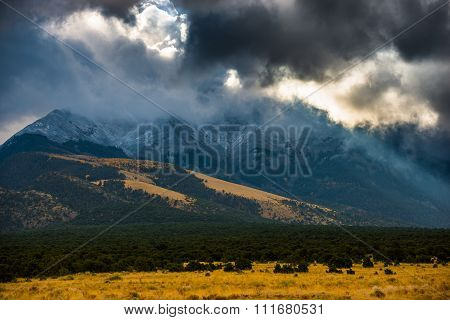 Sun Shining Through The Dark Clouds Over The Mountains Sand Dunes National Colorado