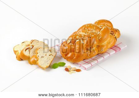 whole and sliced sweet braided bread with almonds on checkered dishtowel