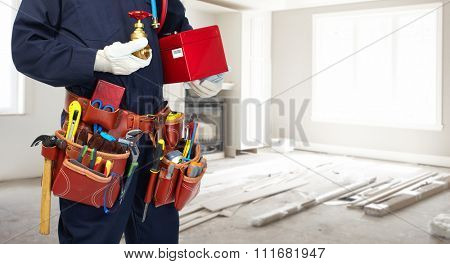 Plumber hands with water tap over kitchen background.