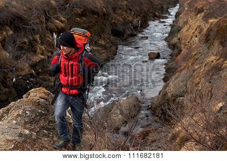 Man in winter gear emerges from gorge  with backpack walking from the fast flowing rocky river, in scenic nature destination