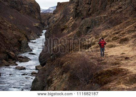 Man hikes alone with backpack and winter gear walking along fast flowing rocky river, in scenic nature destination