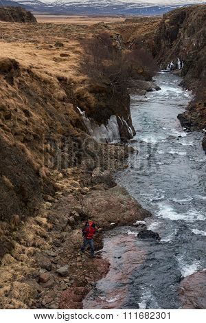 Solo independent hiker man attempting icy river crossing while trekking outdoors isolated and deserted