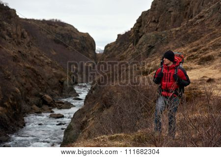 Man on solo camping trip with backpack and winter gear walking along fast flowing rocky river, in scenic outdoor nature destination