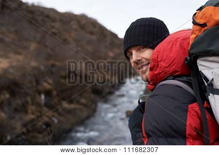 Smiling portrait of a man hiking in winter with beanie jacket and backpack on cliff overlooking a river