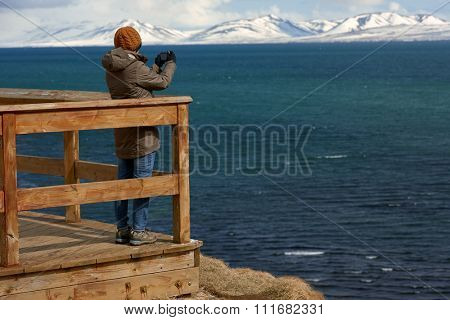 Tourist standing on wooden lookout point deck taking a photo of the beautiful coastal scenery with snow capped mountains in background