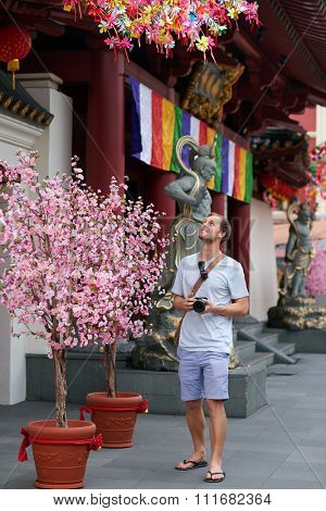 Caucasian tourist looking at a chinese temple, a traditonal religious heritage monument attraction in chinatown of modern asian city singapore